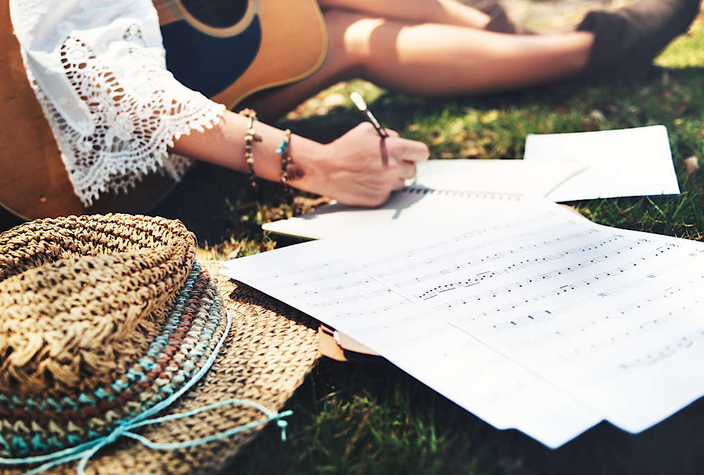 Someone sitting on grass on a sunny day, holding an acoustic guitar and writing sheet music